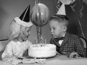 1960s-boy-blowing-out-candles-on-birthday-cake